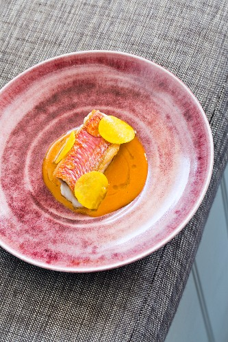 Red mullet with thinly sliced kohlrabi and Porthilly sauce in a restaurant