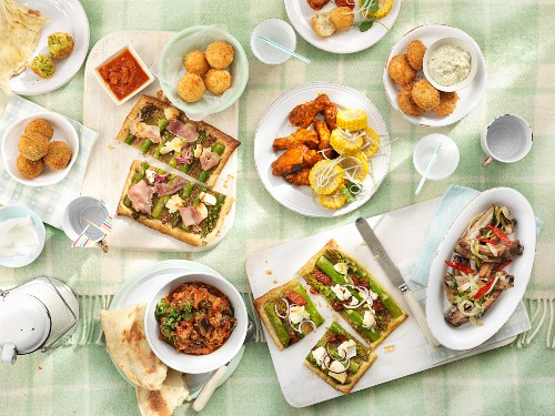 A picnic featuring rice balls, spicy chicken wings, fish balls, ratatouille, ribs, vegetable tart, unleavened bread and falafel