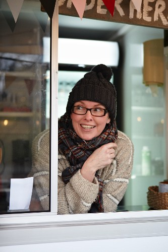 A sales assistant in a kiosk wearing knitted hat