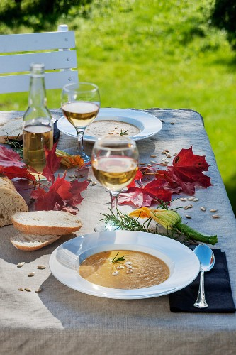 Apple and pumpkin soup outside on an autumnal table