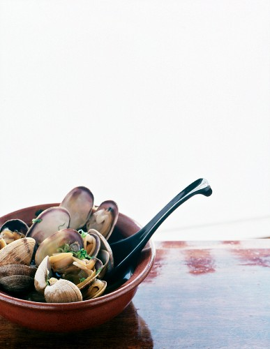 Steamed Pacific clams in broth with chopped Spring onions