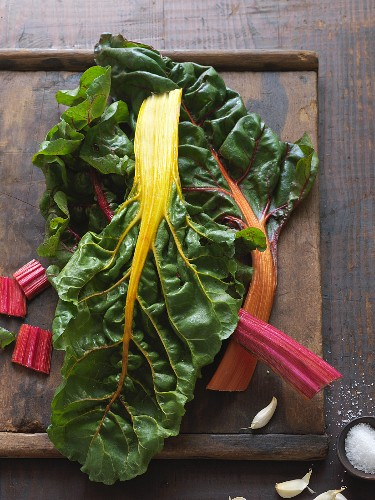 Colourful chard leaves on wooden chopping board