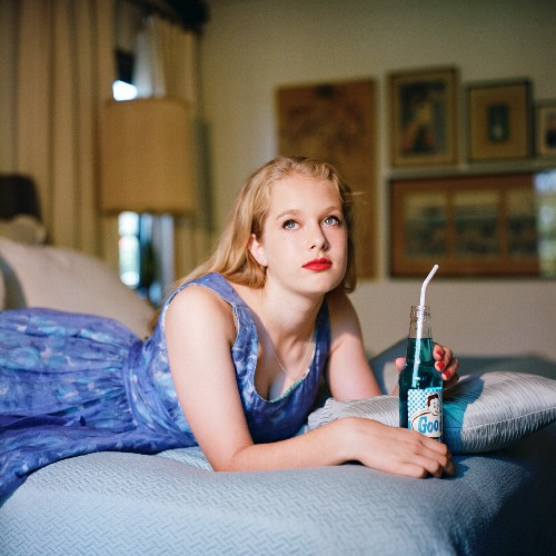 Blonde girl lying on bed with bottle of soda, looking up