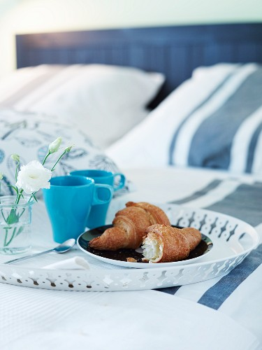 Croissants and blue mugs on a round metal tray for breakfast in bed