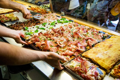 Various pizzas on display in a pizzeria (Rome, Italy)