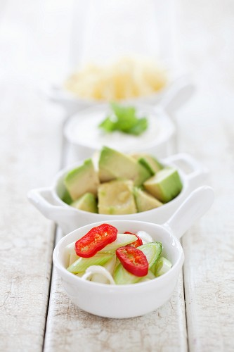 Various toppings: spring onions, chilli rings, avocado, cheese and sour cream