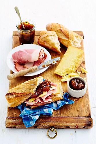 Brotzeit mit Mango-Apfel-Chutney, Schinken, Käse und frischem Baguette auf rustikalem Holzbrett