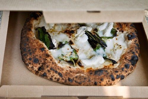 A pizza topped with mozzarella, basil and garlic in a food truck (USA)