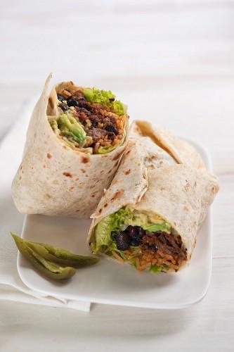 Mit Bohnen, Rindfleisch, Guacamole, Salat und Tomatenreis gefüllter Burrito
