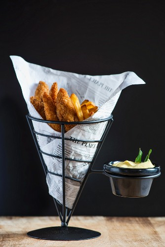 Fried chicken and chips in a paper cone served with mayonnaise