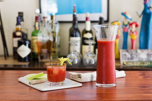 A classic Bloody Mary drink with celery on a table with a home bar in the background