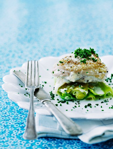 Baked cod on a bed of leek with grated Parmesan cheese, chives and a white wine and cream sauce