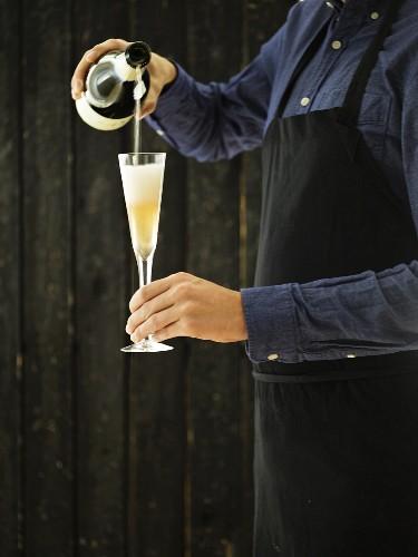 Sommelier schenkt Champagner in eine Champagnerglas ein