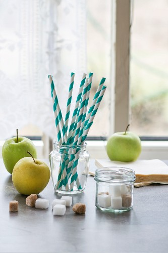 Green apples, sugar cubes and drinking straws in front of a kitchen window