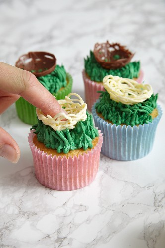 Easter cupcakes being decorated with Easter chocolate nests