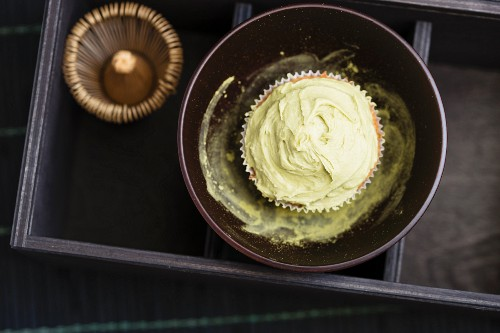 A cupcake with matcha tea frosting in a bowl with matcha tea powder next to a tea whisk