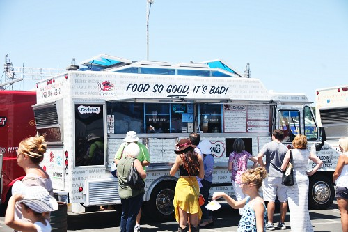Customers buying fast food from a food truck festival in California, USA