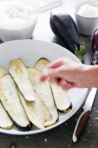 Aubergine slices being sprinkled with salt