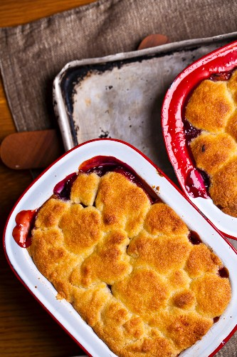 Plum and apple cobbler in enamel tins