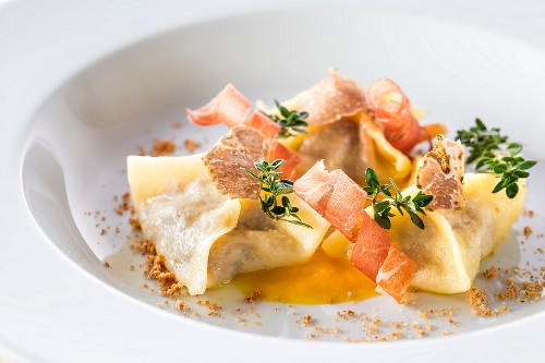 Meat-filled ravioli with pumpkin sauce, bacon and truffle
