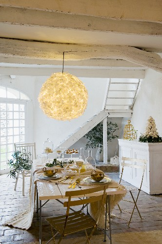 Rustic, whitewashed wooden ceiling with large, floral paper lampshade above table set for Christmas meal