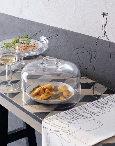 A buffet table with filigree wire objects with fried stockfish and sage under a glass cloche