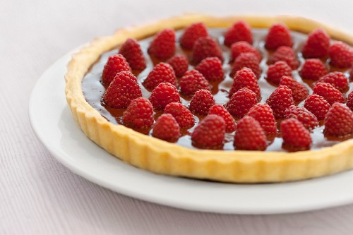 A tart with a shortcrust pastry base, topped with chocolate cream and fresh raspberries