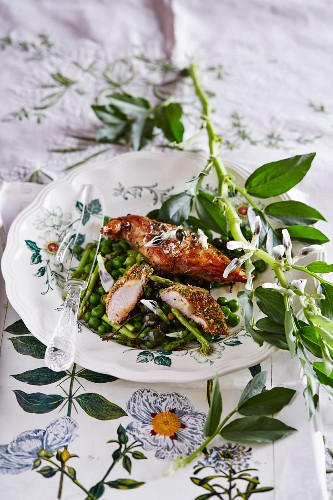 Chicken with an aromatic breadcrumb crust on a bed of spring vegetables with pea flowers