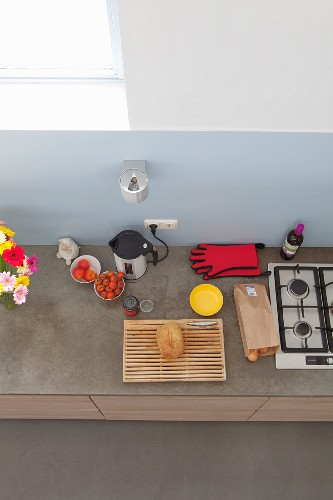 View down onto kitchen counter with pale blue splashback, gas hob and kitchen utensils