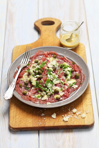 Beef carpaccio with mustard dressing, capers and Parmesan cheese