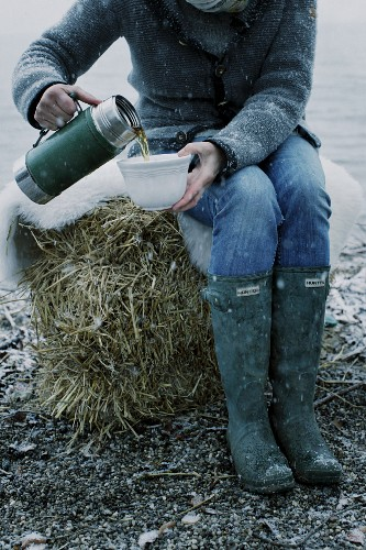 A woman wearing welly boots pouring tea from Thermos flask into a cup