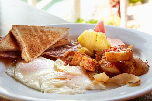 Breakfast of fried eggs, bacon, potatoes, toast and pineapple (Costa Rica)