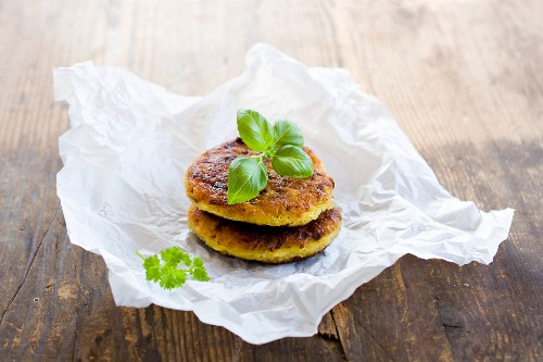 Vegetarian millet burgers with kohlrabi and herbs on a piece of paper