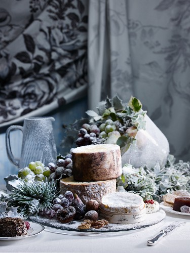 A Christmas table laid with sugared grapes, cheese and jelly