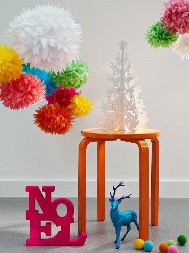 Colourful paper pom-poms hung over a white paper Christmas tree on a stall with a 'Noel' decoration and a neon blue deer on the floor