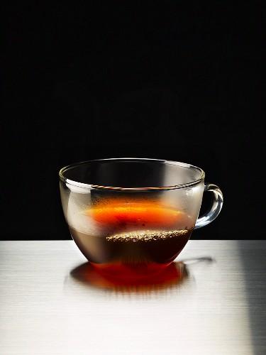 A glass mug of black coffee on a metal surface