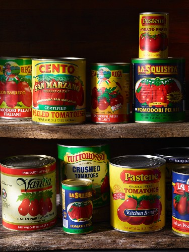 Various types of tinned tomatoes on a wooden shelf