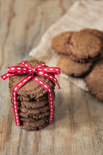 Gingersnap biscuits with a red ribbon on a wood surface