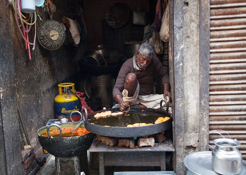 A street vendor preparing Jalebi (deep-fried rings, India)