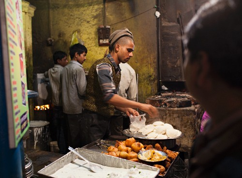 Traditionelles Street Food (Reisfladen und Aloo Tikki Bratkartoffeln) bei einem Straßenstand in Varanasi, Indien