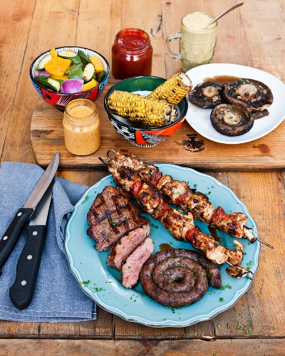 Corn cobs and meat, chicken tikka skewers and barbecued steaks at The Backyard Grill Lounge, Sea Point, South Africa