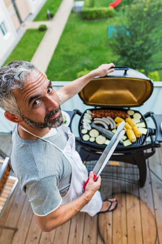A man barbecuing on his balcony