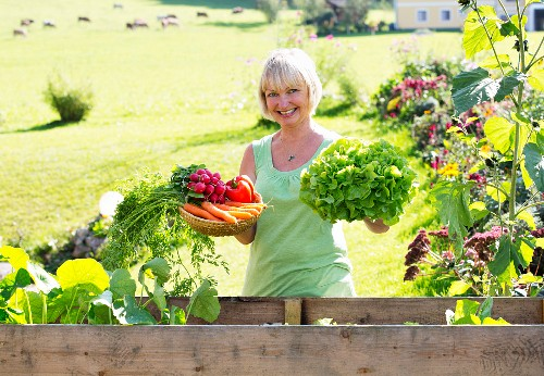 A happy woman showing off her vegetable harvest