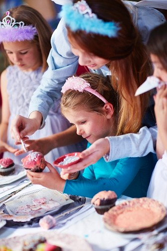 Little girls decorating cupcakes at birthday party