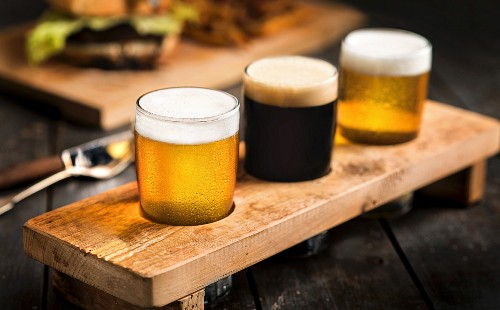 Three types on beer in a wooden holder; light beer, dark beer and India Pale Ale
