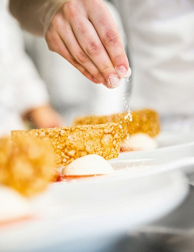 A chef putting the finishing touches to a dessert