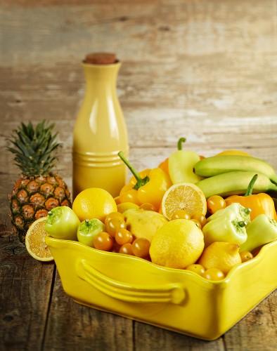 Verschiedene gelbe Früchte und Gemüsesorten in Keramikschale