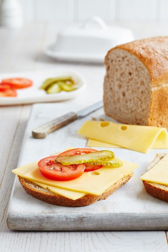 A slice of wholemeal bread topped with tomatoes, gherkins and Emmentaler cheese