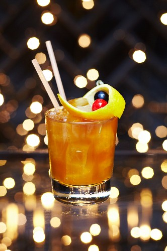 A Christmas cocktail with oranges, orange peel and a maraschino cherry