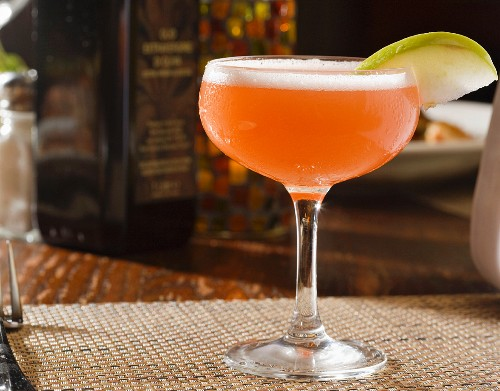 A pink cocktail made with tequila and garnished with an apple slice